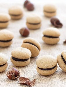 Baci di Dama ( Italian Hazelnut Cookies): two buttery hazelnut cookies sandwiched together with a dollop of dark chocolate. Perfect with a cup of coffee or espresso!