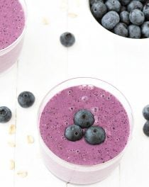 two oatmeal blueberry smoothies and a bowl of blueberries