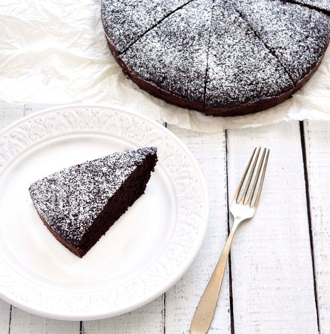 sliced chocolate cake and a slice on a plate. Top view