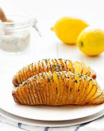 Two baked hasselback potatoes on a white plate