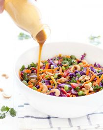 Pouring the peanut dressing over the top of a big bowl of chopped asian salad
