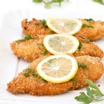 Three oven baked chicken breasts with a slice of lemon on top
