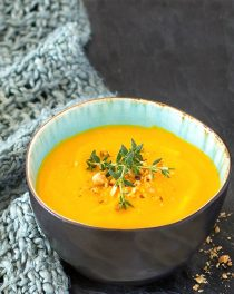 ginger turmeric carrot soup in a black bowl garnished with fresh thyme