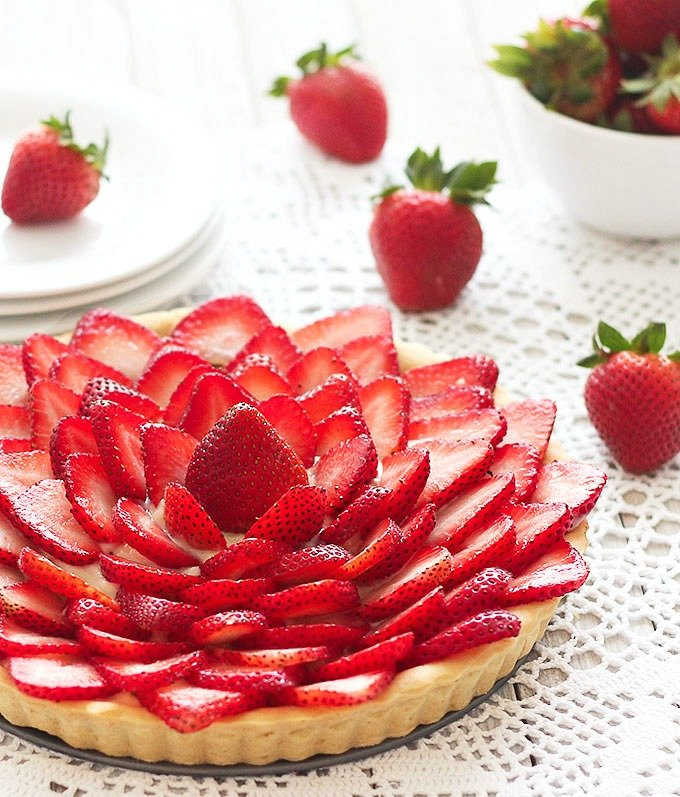 strawberry tart with plates and a bowl of fresh strawberries in the background - close up