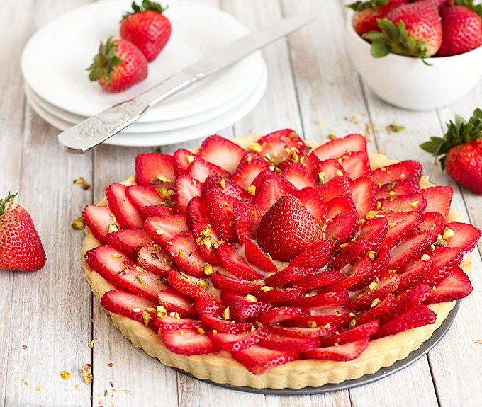 strawberry tart on a white wooden table with plates and a bowl of fresh strawberries in the background