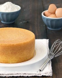 Italian sponge cake on a white plate. A bowl with flour and egg shells in the background