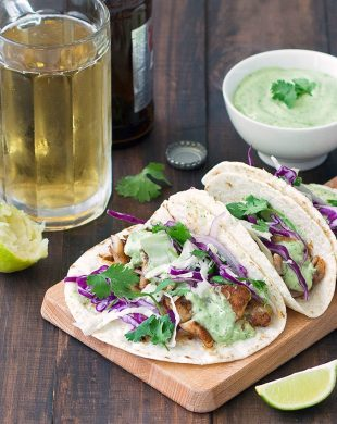 Blackened fish tacos on a wooden board and a glass of beer in the background