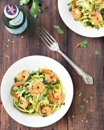 Two white bowls with zucchini noodles and shrimp, a bottle of water, and a fork on a wooden table.
