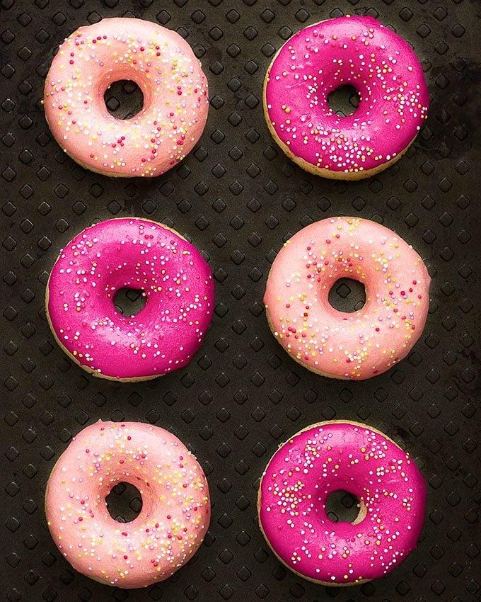 Six vanilla glazed baked donuts on a black tray
