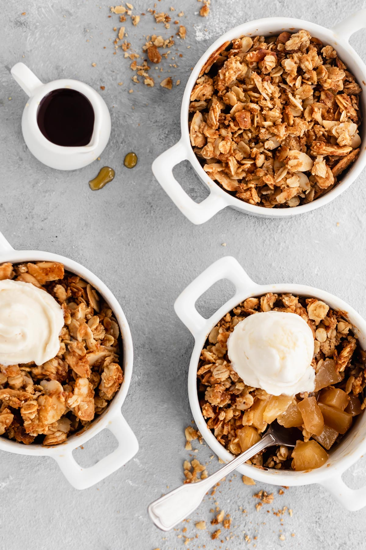 Easy Individual Apple Crisps: a sweet, cinnamon spiced apple filling with a buttery, crunchy topping! Serve them warm with vanilla ice cream and perhaps a drizzle of salted caramel sauce for a quick and delicious dessert!