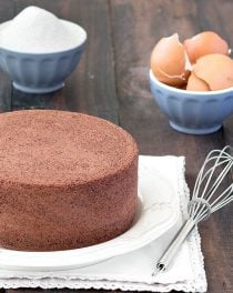 Chocolate sponge cake on a white plate and a whisk next to it.