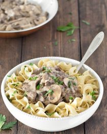 Noodles and beef stroganoff sprinkled with chopped parsley in a white bowl