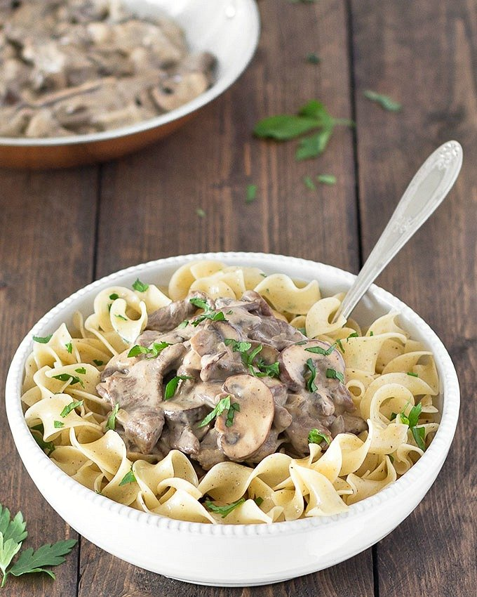Noodles and beef stroganoff in a white bowl with a fork