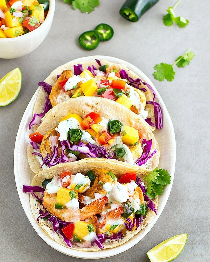 Spicy shrimp tacos with mango salsa and cilantro lime sauce. An easy, flavorful and delicious meal ready in 20 minutes!