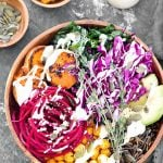 Vegan buddha bowl garnished with fresh thyme and drizzled with lemon tahini dressing