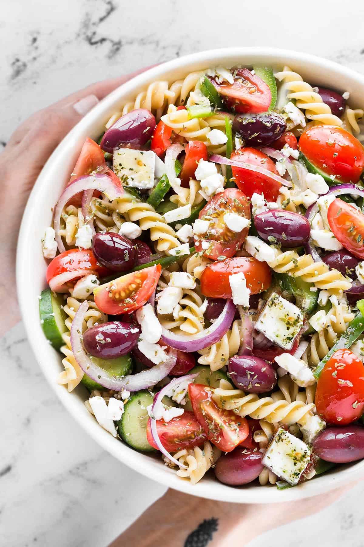 Hands holding a bowl of Greek pasta salad