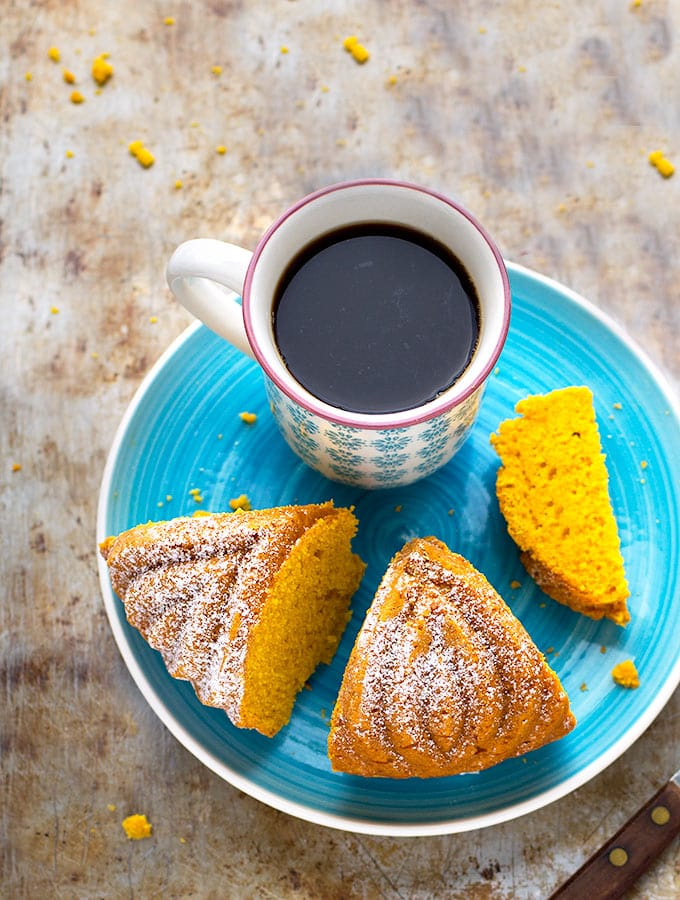 Easy Pumpkin Bundt Cake- Perfectly moist, soft, tender, and bursting with fall flavors! A sliced bundt cake sits on a turquoise plate with a cup of strong black coffee.