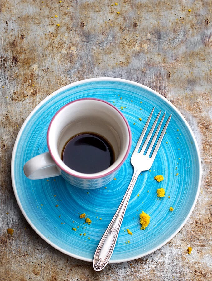 An empty turquoise plate with the remnants of a delicious bundt cake and an almost-empty coffee cup.