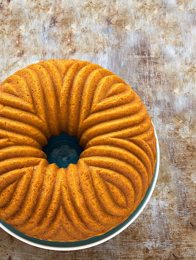 A beautifully orange pumpkin bundt cake sits on a wooden table.