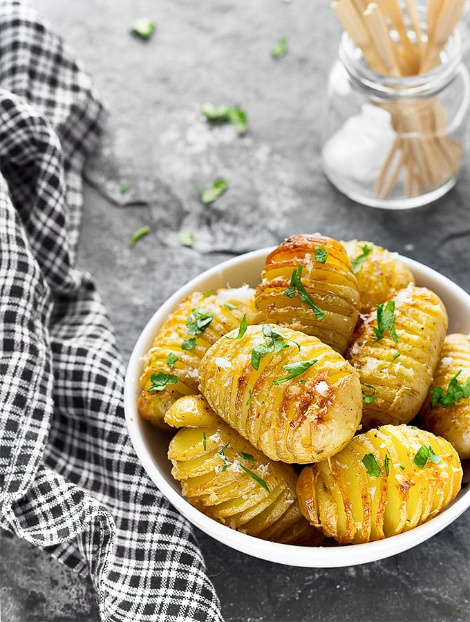 A white bowl with mini Hasselback potatoes and a black and white napkin