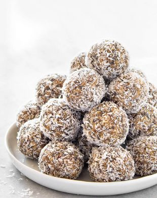 A white plate with a stack of lemon coconut energy balls