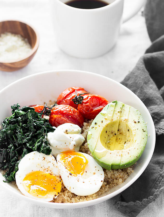 A savory quinoa breakfast bowls, a cup of coffee, and a gray napkin