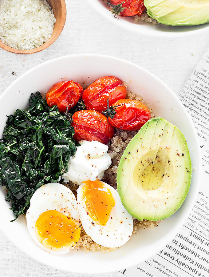 Two savory quinoa breakfast bowls and a newspaper