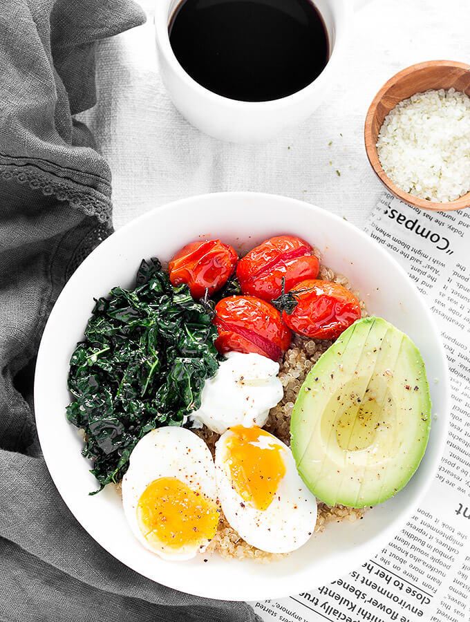 A savory quinoa breakfast bowls, a cup of coffee, and a newspaper