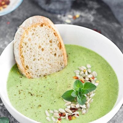 A bowl of broccoli white bean soup and a slice of bread