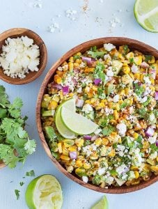 A bowl of Mexican street corn salad, a lime, a small bowl of feta cheese, cilantro.