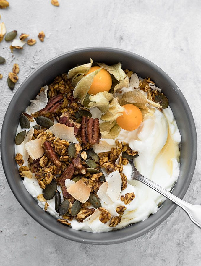 A crunchy and flavorful Pumpkin Spice Granola scented with pumpkin flavor, warm fall spices, and studded with pumpkin seeds, pecans, and unsweetened coconut flakes. This easy recipe is perfect for healthy breakfasts and snacks. Recipe at aseasyasapplepie.com