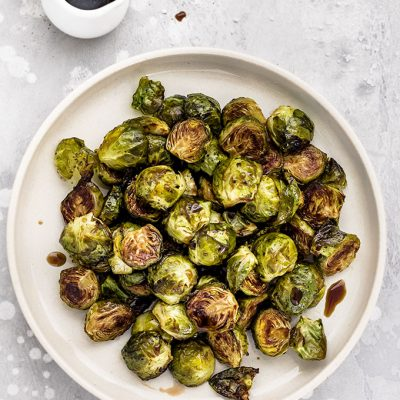 a plate of oven roasted Brussels Sprouts drizzled with balsamic vinegar and honey