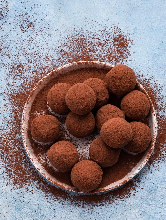 Almond chocolate truffles coated with raw cacao powder on a white plate