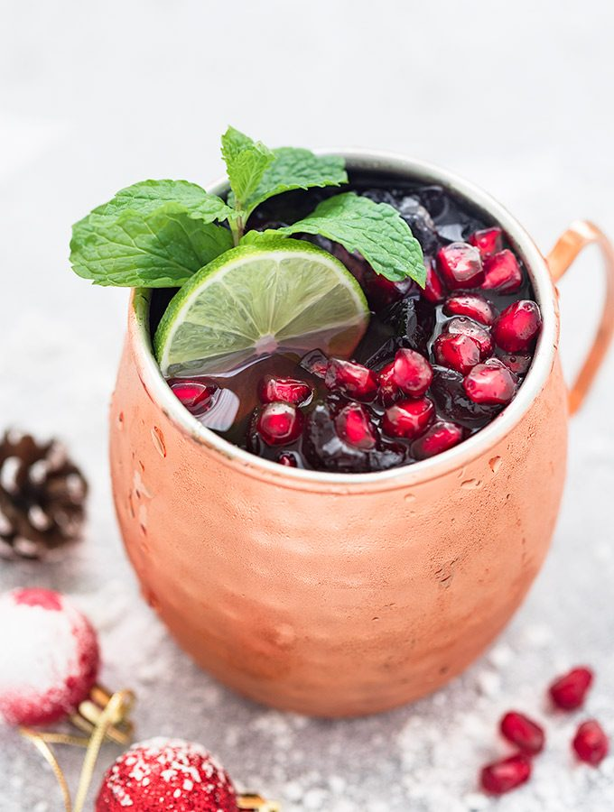 Pomegranate Moscow mule in a copper mug  garnished with fresh mint leaves, pomegranate arils and lime