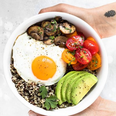 hands holding a quinoa breakfast bowl