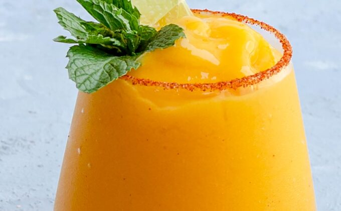 A glass of frozen mango margarita garnished with lime and mint