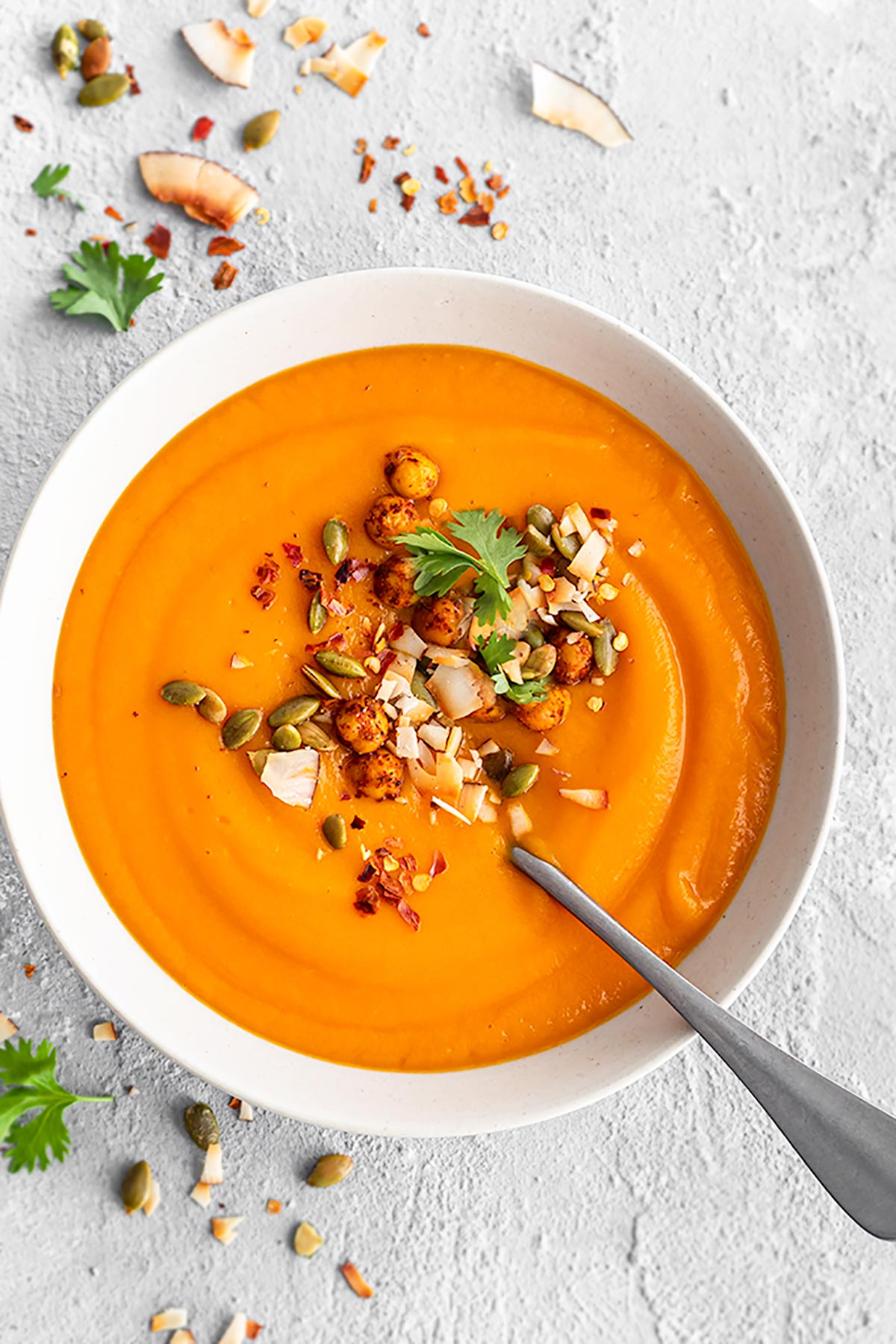 Bowl of sweet potato soup garnished with roasted chickpeas, toasted coconut flakes, roasted pumpkin seeds, red pepper flakes, and cilantro.  Top view