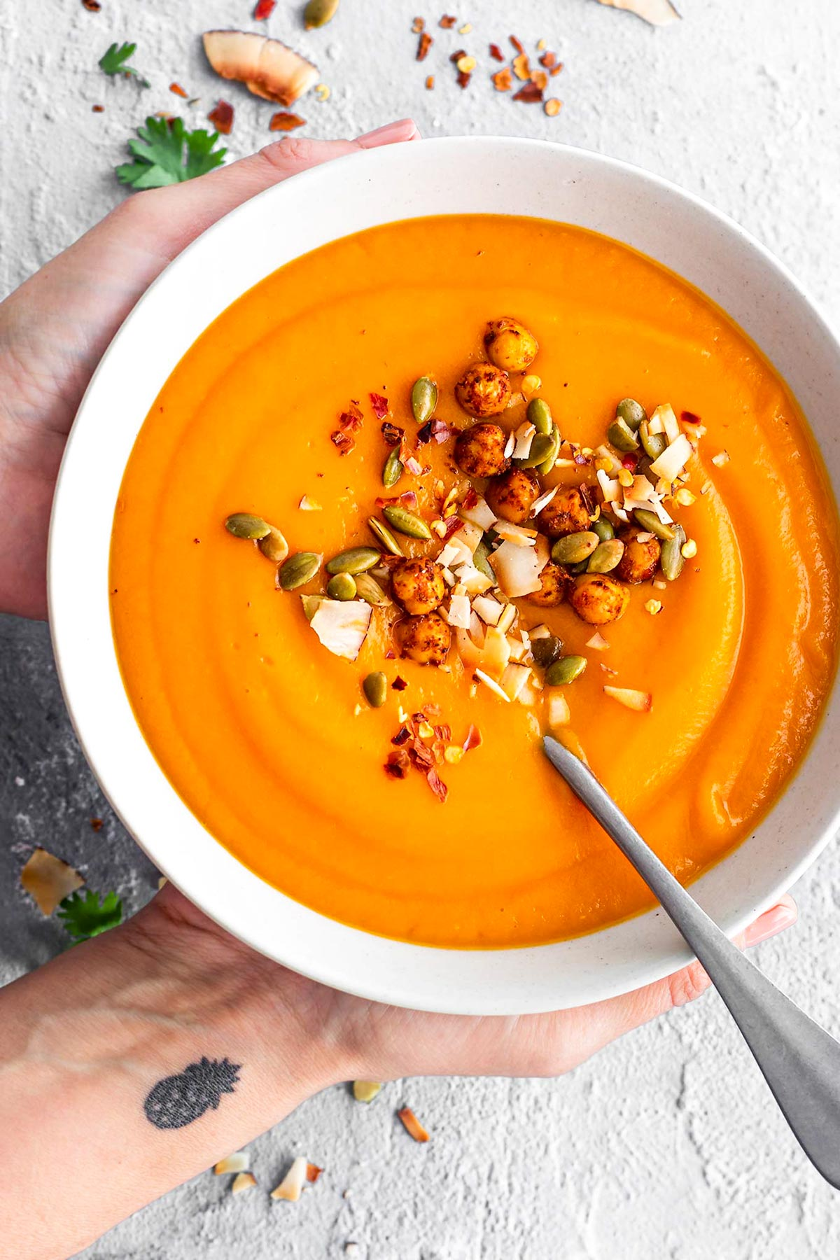 Hands holding a bowl of sweet potato soup garnished with roasted chickpeas, toasted coconut flakes, roasted pumpkin seeds, and red pepper flakes.  Top view